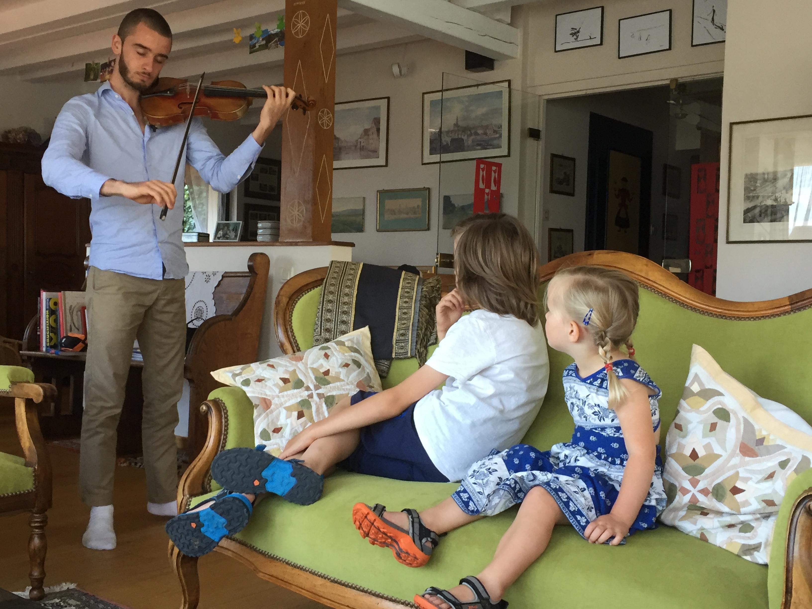 Deux des petits-enfants de Marie-Suzanne Weick-Voelckel, fascinés, écoutent Elie jouer le violon de leur arrière-grand-père